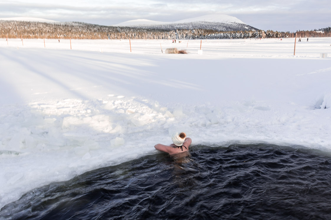 Baignade dans l'eau glacé d'un lac gelé en Laponie.