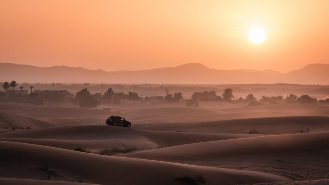 Voiture roule au coucher du soleil dans les dunes du désert au Maroc.