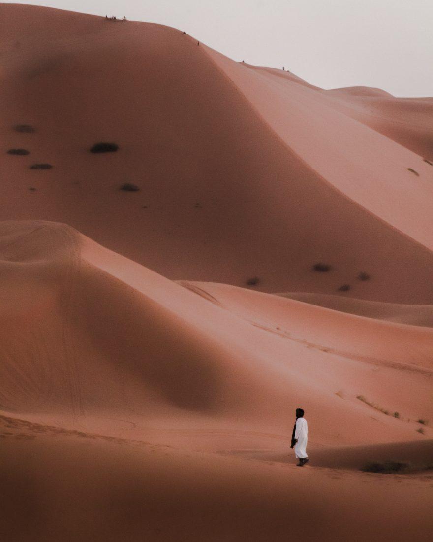 Un homme marche au pied d'une grande dune dans le désert marocain.